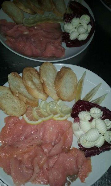 un piatto con carpaccio di pesce, fette di pane e limone