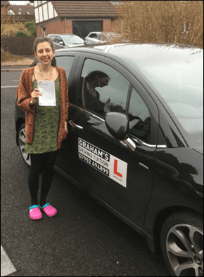 Student stood next to a car, who has passed her driving test.