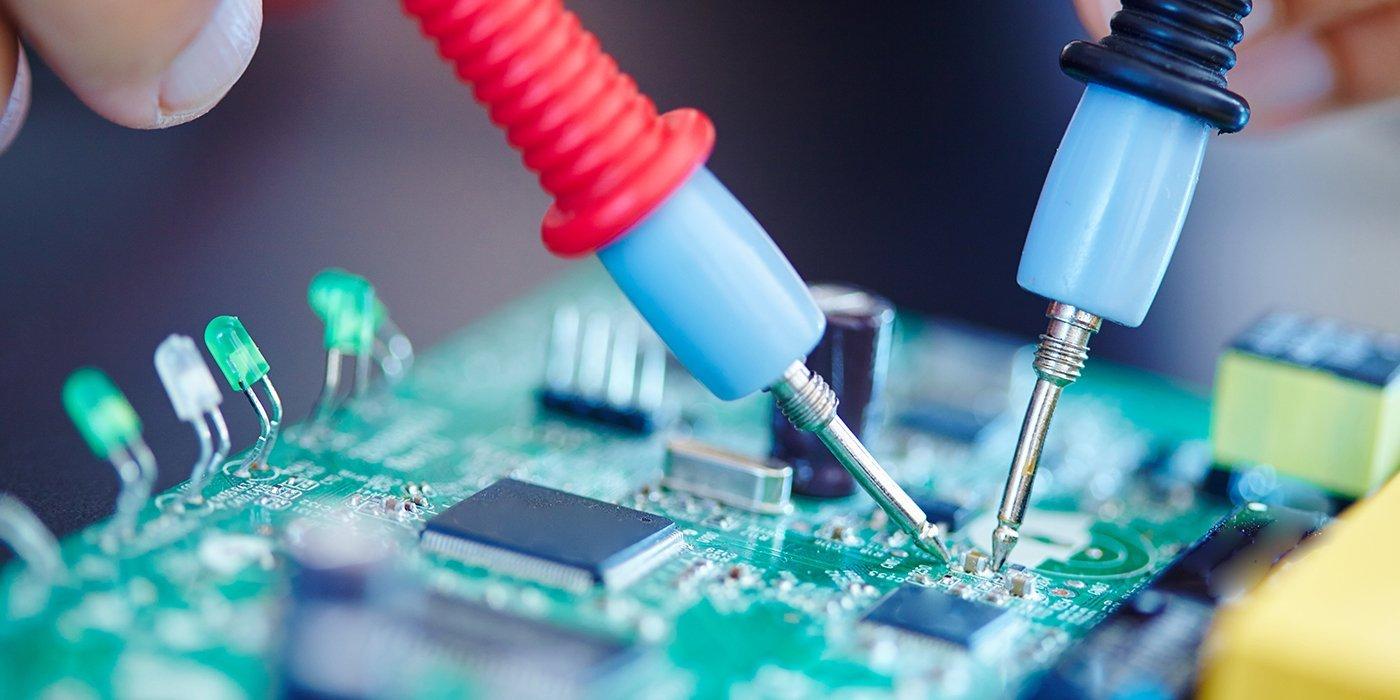 due mani con in mano due tester azzurri, uno con il manico rosso e l'altro blu appoggiati su un circuito elettronico di una scheda madre di color verde