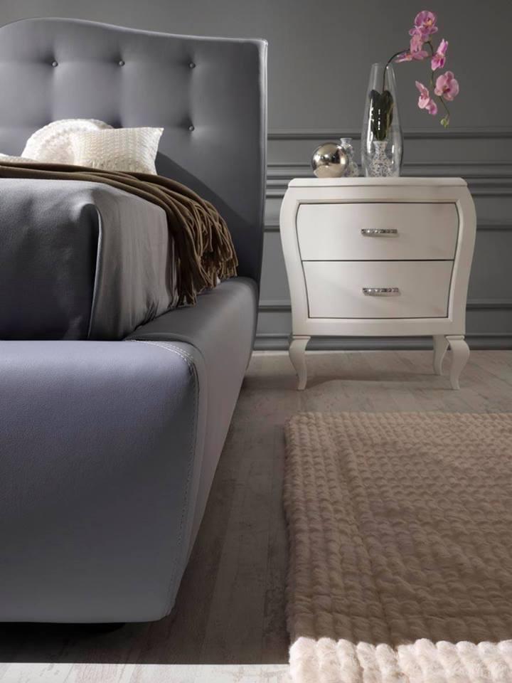 Camera da letto arredato con letto in grigio e comò bianco
