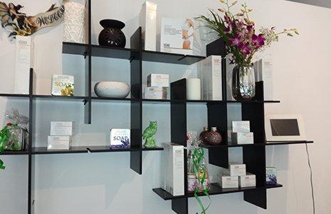 Una mensola in stile giapponese con scatole di creme di bellezza e fiori