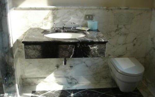 un lavabo in marmo nero a sfumature bianche, un wc e i muri in marmo