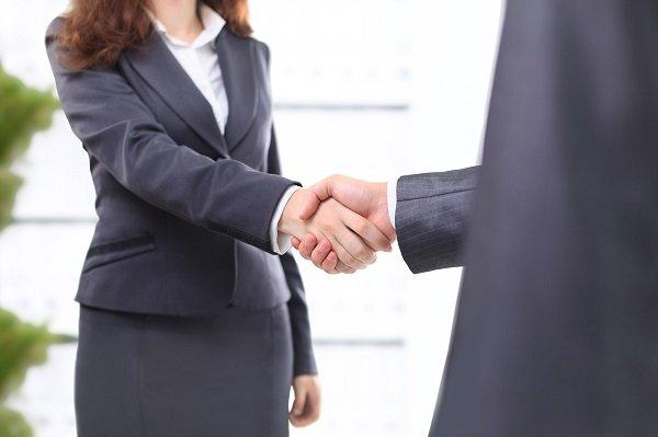 Stretta di mano tra uomo e donna in vestito
