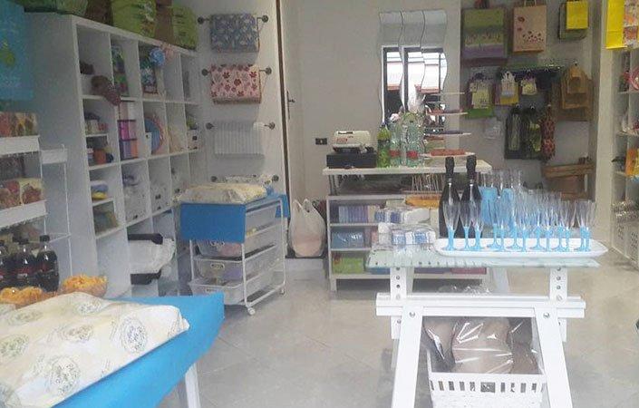 Interno del negozio con un tavolino bianchi con bicchieri di vetro e azzurri esposti con accanto delle bottiglie e accanto articoli da merceria
