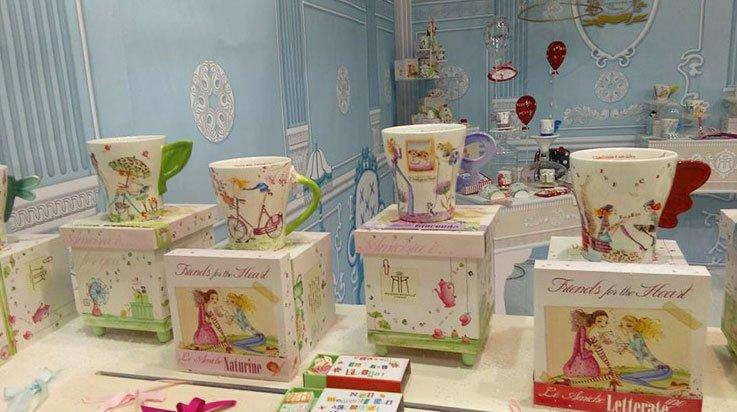 esposizione di tazze sopra a delle scatole che raffigurano il disegno di due donne stile fumetto che bevono con una tazzina. La stanza ha dei muri azzurri e degli ornnamenti bianchi dipinti