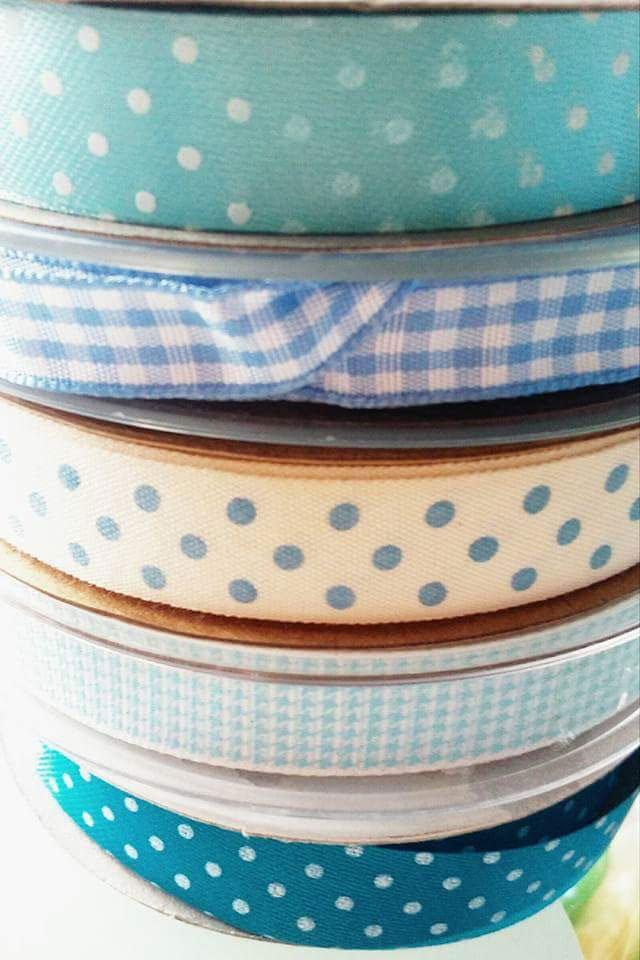 serie di nastri di stoffa uno sopra l'altro azzurri,gialli, a pois e a quadretti