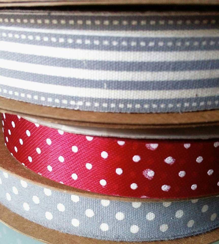 tre nastri, uno grigio con puntini bianchi, l'altro rosso a pois e l'ultimo grigio con righe bianche