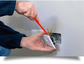 an electrician working on a wall socket