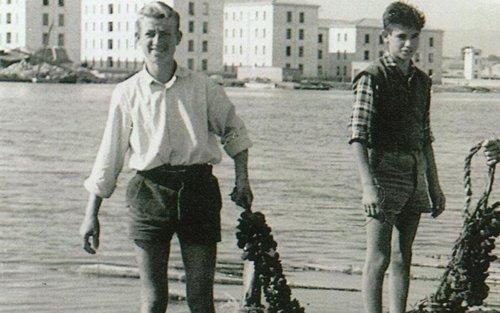 foto antica di due persone che tengono in mano un grappolo di cozze