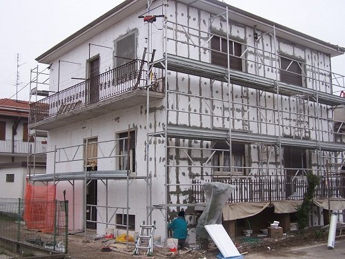 Vista d'angolo di casa circondata con ponteggi