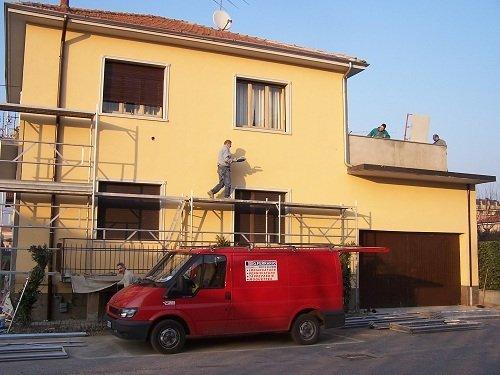 Casa ridipinta con ponteggi e un operaio al lavoro