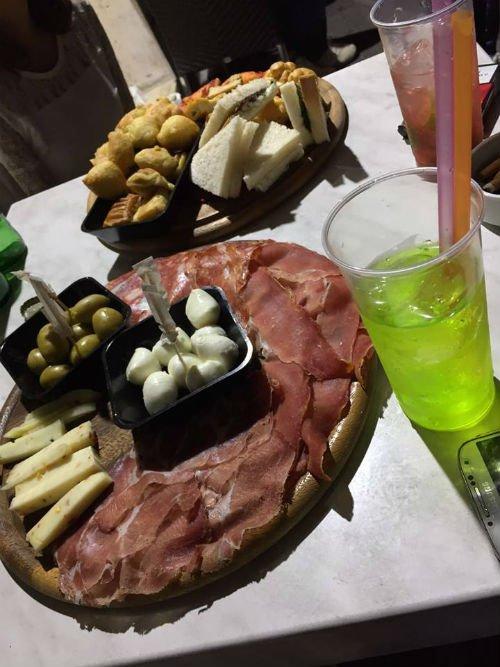 un tagliere con dei salumi, formaggi e delle olive