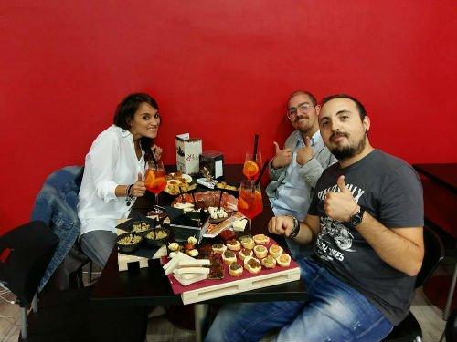 una donna e due uomini seduti al tavolo con dei cocktail e gli antipasti