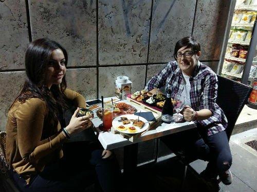 due donne sedute al tavolo con dei cocktail e gli antipasti