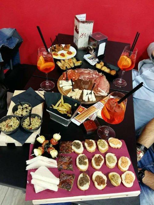 un tavolo con dei cocktail, patatine fritte  e gli antipasti