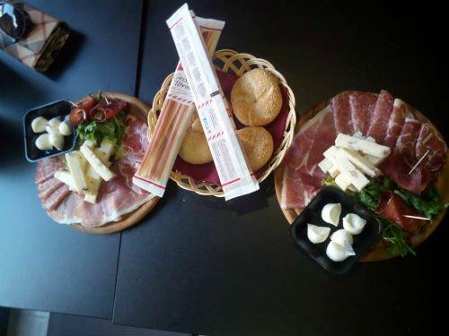 un tavolo con dei salumi, formaggi , grissini e del pane