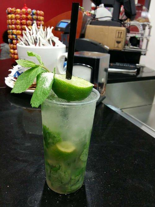 un bicchiere di cocktail con lime e delle foglie di menta