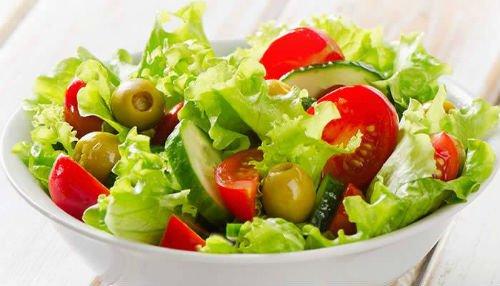 un'insalatiera con lattuga, pomodorini e delle olive verde