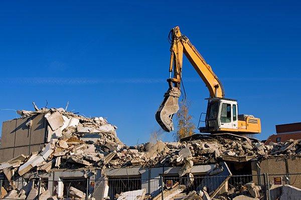 Pala escavatore portando a termine una demolizione
