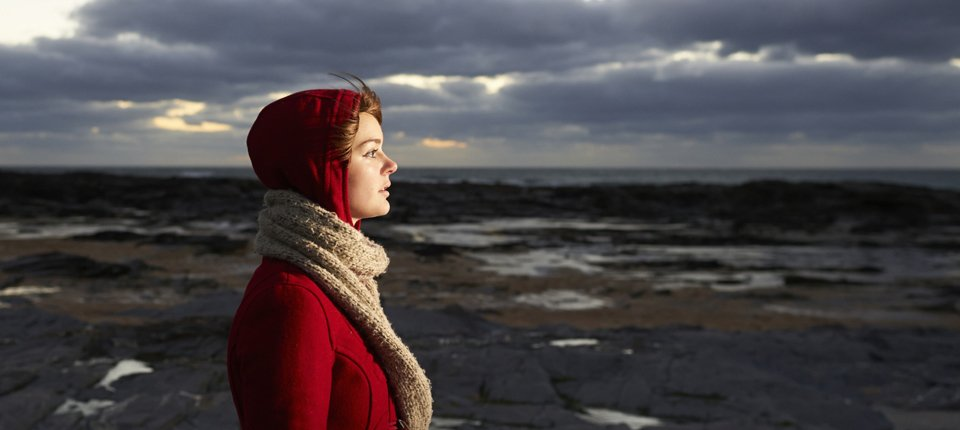A lady in a red coat with the hood up, and a camel scarf, standing on a rocky beach on a dark windy day