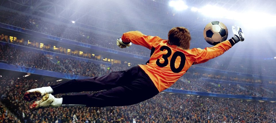 A goalkeeper in an orange shirt, leaping to save a ball, in a stadium crowded with people