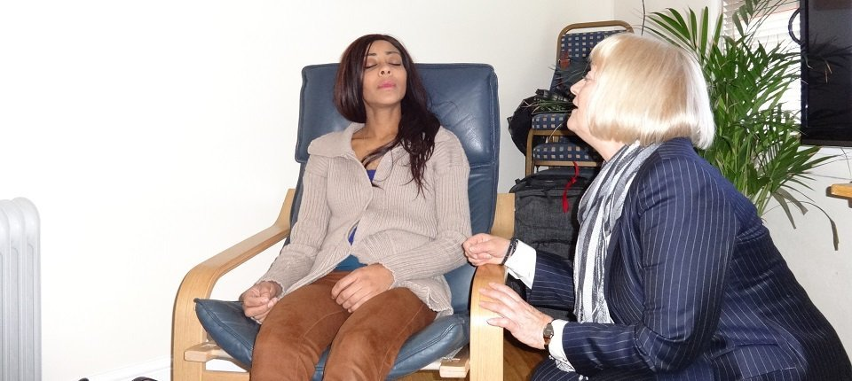 A lady undergoing hypnotherapy, relaxing in a chair with her eyes closed while the therapist talks to her