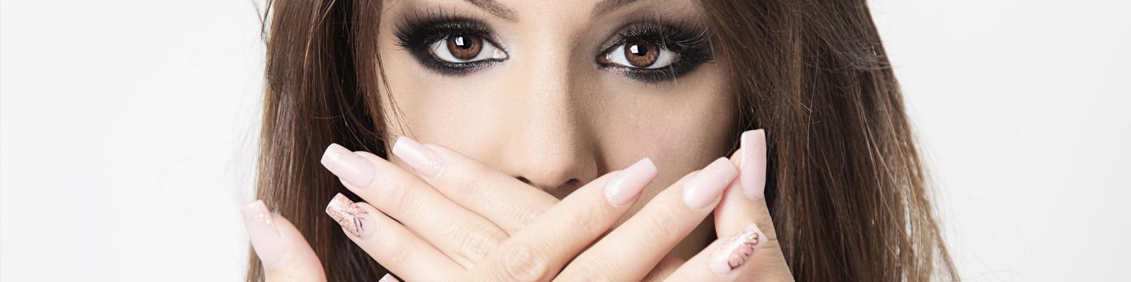 Modella con unghie ricostruite e mani sulla bocca