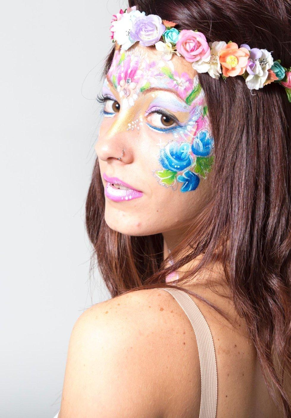Modella con fiori dipinti sul viso e corona di fiori in testa
