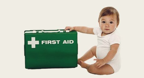 baby sitting near a first aid kit