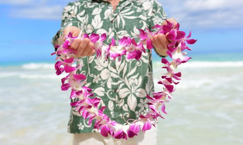Man providing traditional Hawaiian lei greeting in Oahu