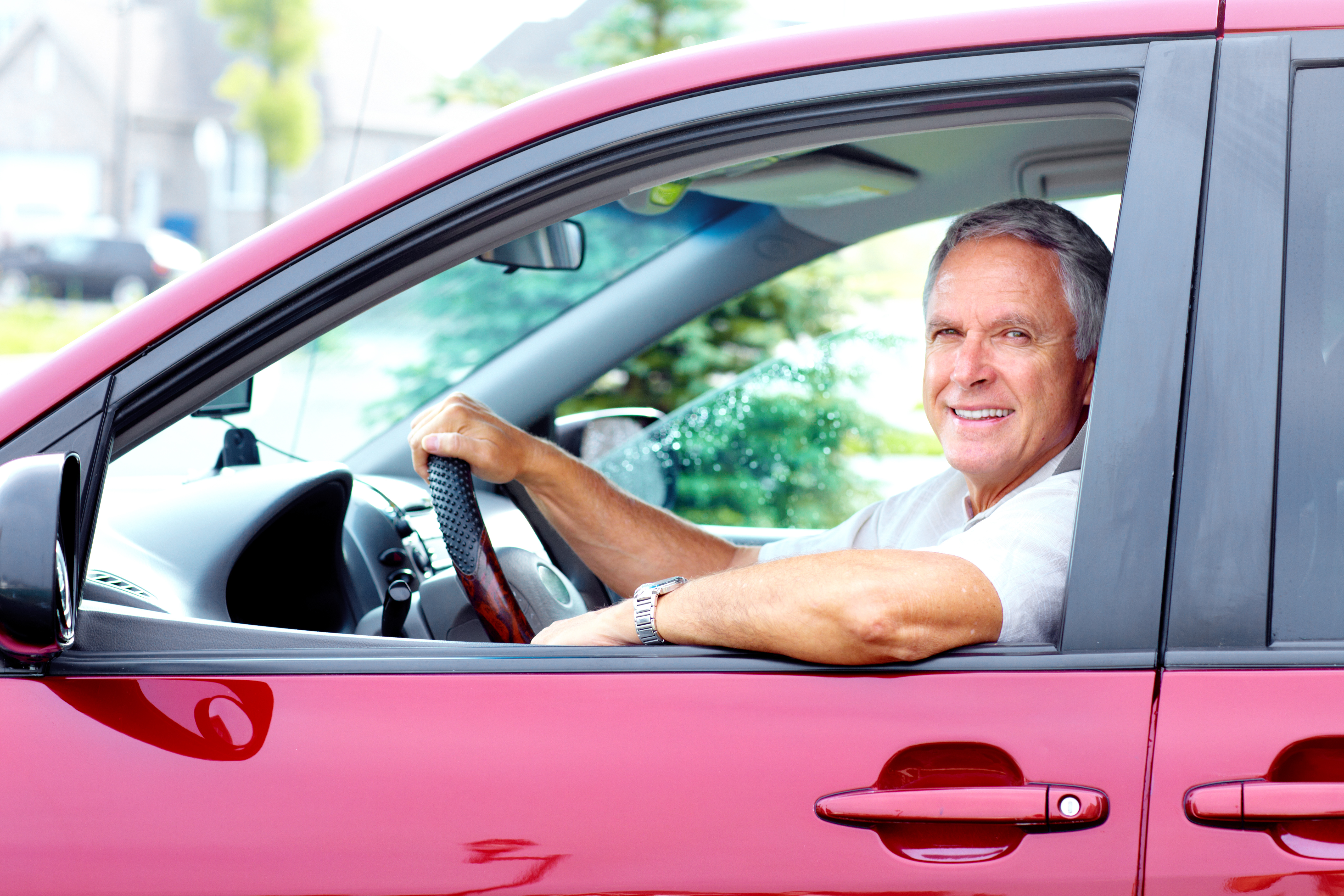 Senior driver happily driving his car with a renewed license