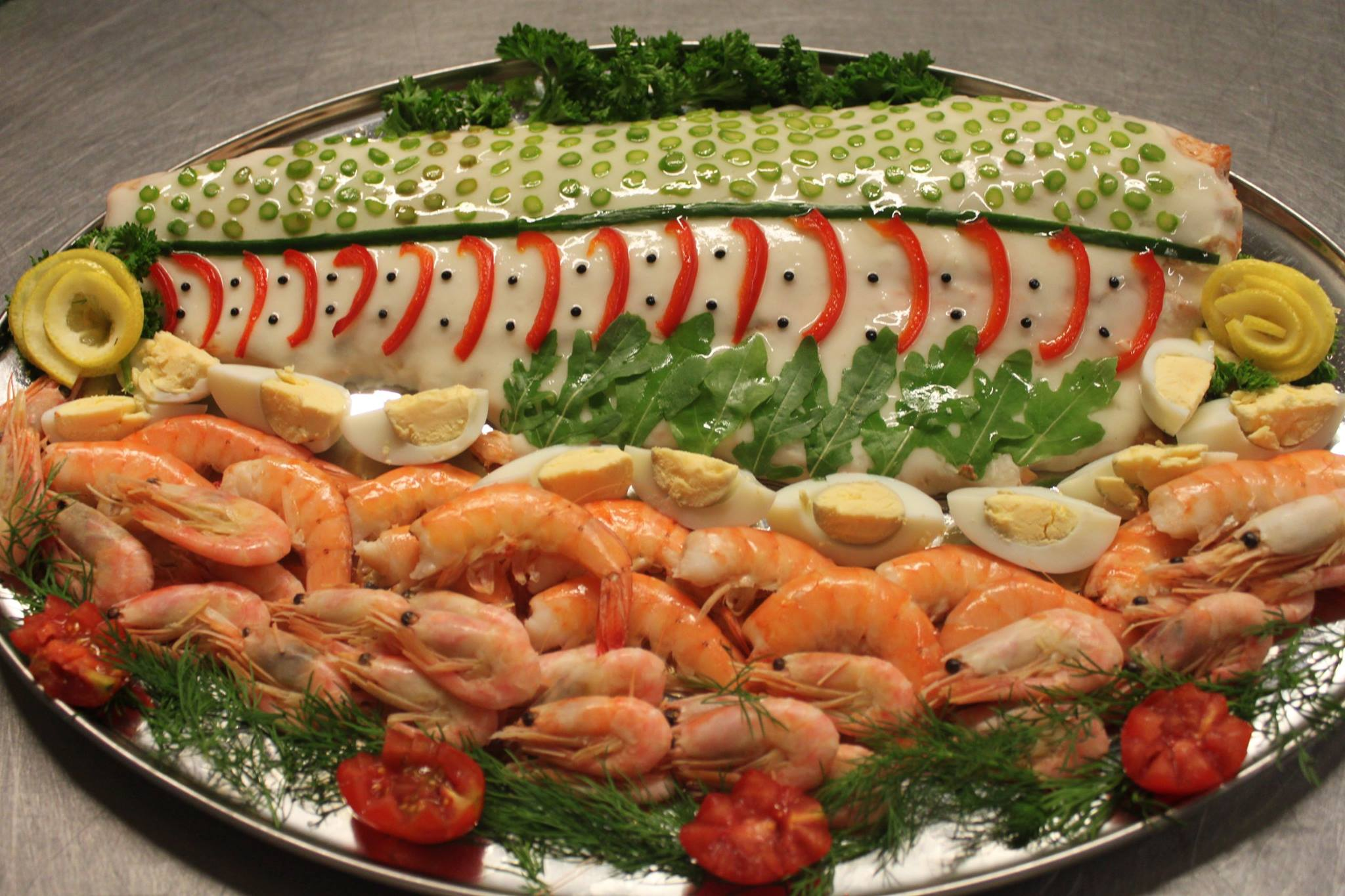 Fillet of salmon coated in a chaud froid sauce and decorated red peppers and slices of cut asparagus garnished with whole prawns and boiled eggs.