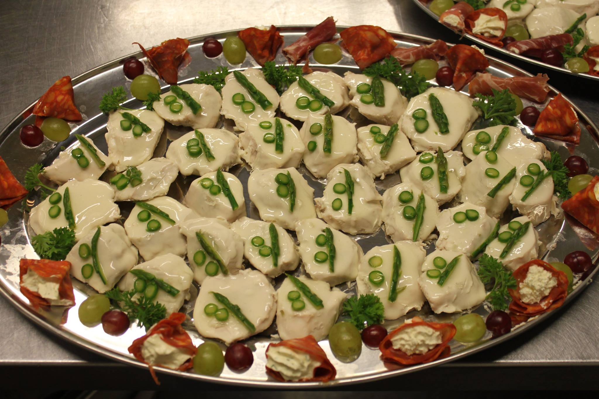 Chicken coated in a chaud froid sauce garnished with asparagus tips with chorizo filled with cream cheese with fine herbs ready for the next buffet.