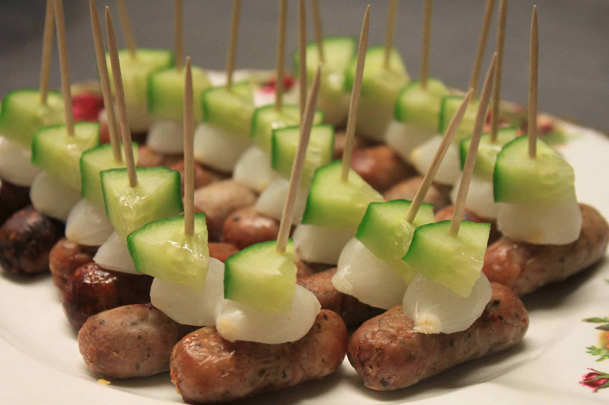 Cocktail sausages with pickle silverskin onions and cucumber on sticks.
