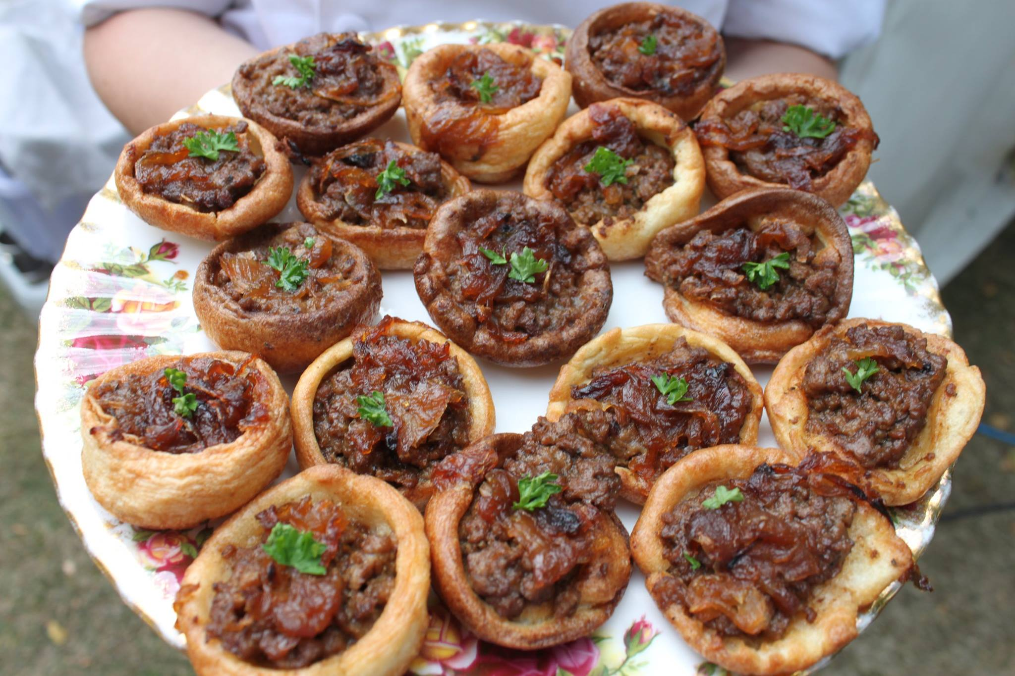 Homemade Yorkshire puddings filled with best minced beef and topped with caramelized onions canapes.