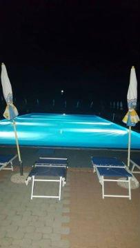vista di una piscina con due sdraio