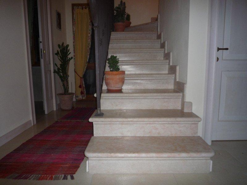 Entrata di una casa con scala al piano superiore di marmo bianco venature in rosa