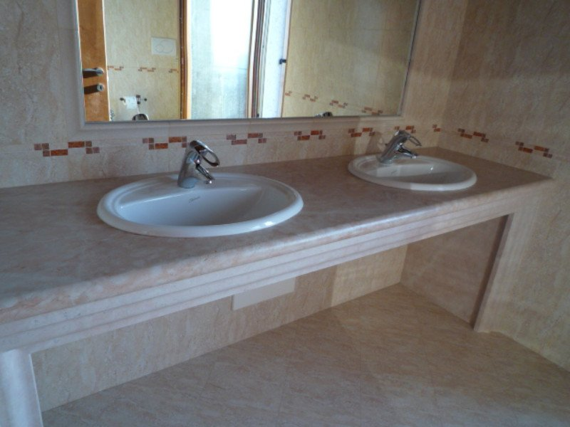 Bagno con due lavabi bianchi ,un grande specchio e pareti,mobile e pavimento marmo bianco e rosa