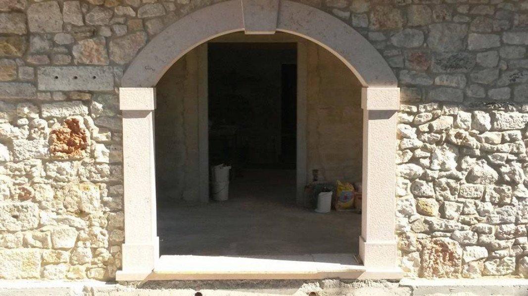 Grande porta di accesso a una casa con arco di mezzo punto realizzata in marmo