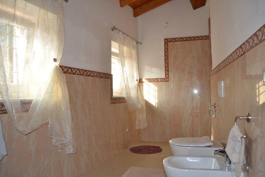 Bagno fatto in marmo fino a media parete con orlatura di piastrelle di marmo con design