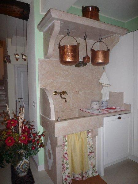 Rincon di una cucina dove un pezzo di marmo che comprende una ripiano,il rivestimento di pareti e il lavabo sono in marmo. Vecchi utensili di rame decorano lo spazio