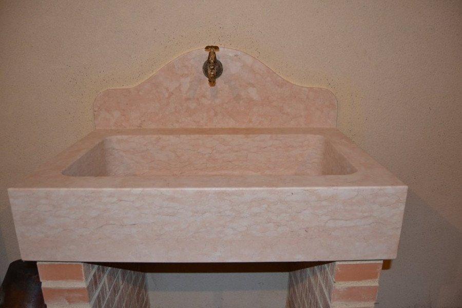 Lavabo di marmo rosa e bianco su due pile di mattoni