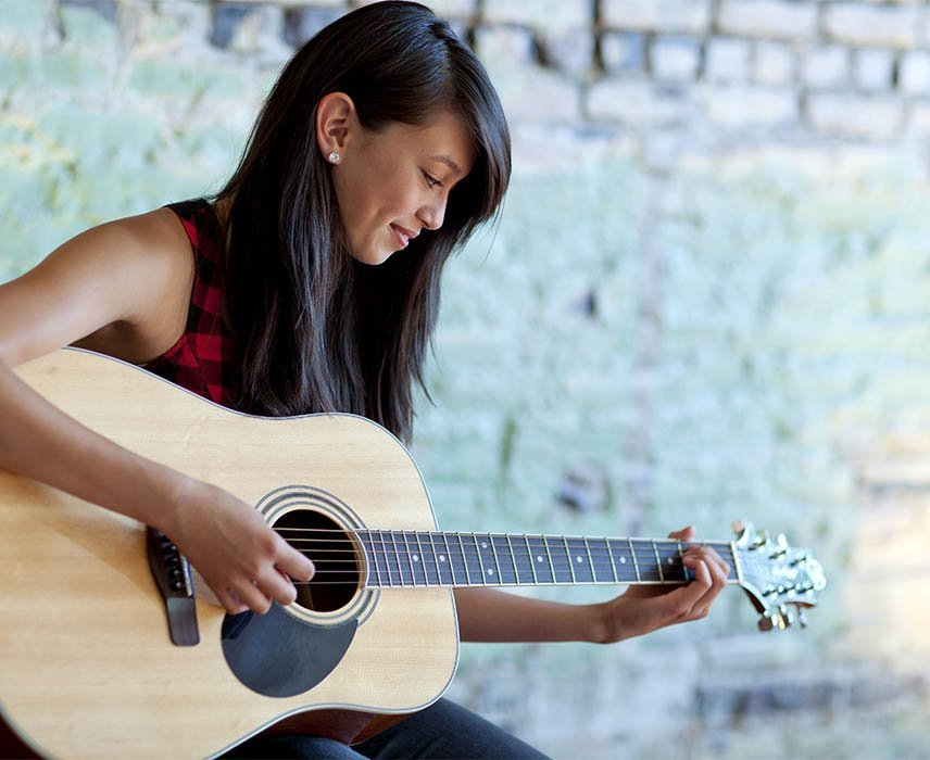 a lady practicing guitar