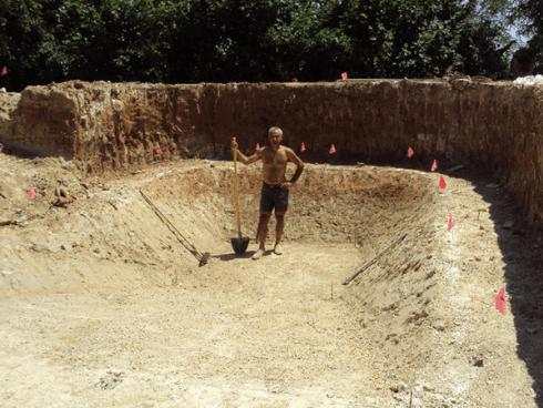 Un muratore con una pala in uno scavo