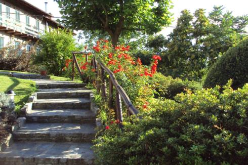 Una scalinata con un corrimano in legno e dei fiori sulla destra
