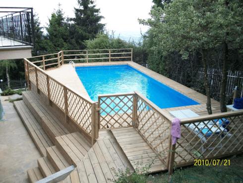 Una piscina circondata da delle passerelle in legno e sulla sinistra una ringhiera