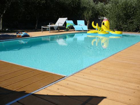 Una piscina circondata con delle passerelle in legno e degli sdraio di color azzurro sulla sinistra