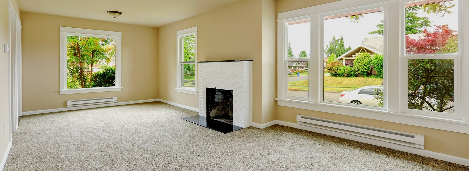 A large empty room with cream walls and white brick fireplace, and white windows overlooking a quiet tree-lined road