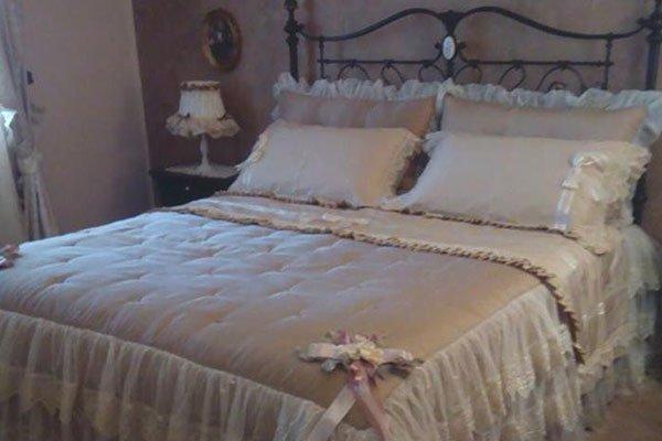 una camera da letto stile antico con un letto matrimoniale in ferro battuto con un piumone di seta trasparente e sulla sinistra un comodino con una lampada