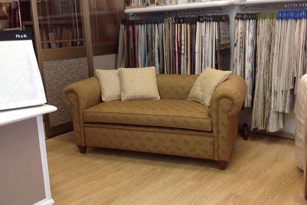 un divano di color arancione con tre cuscini gialli e dietro un esposizione di stoffe appese a un appendi abiti
